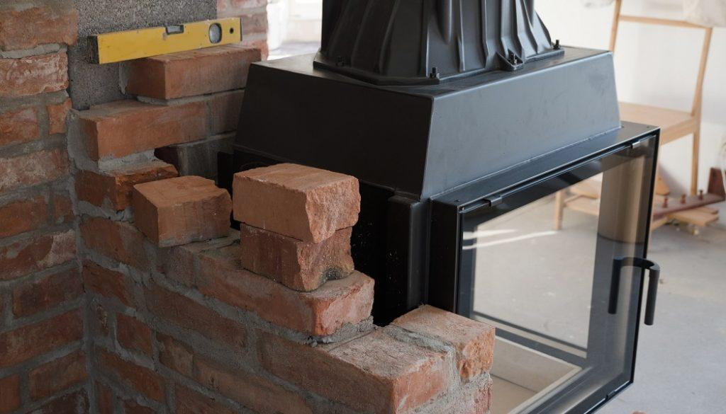 brick wall border for a wood-burning stove or fireplace under construction in the interior fitting area